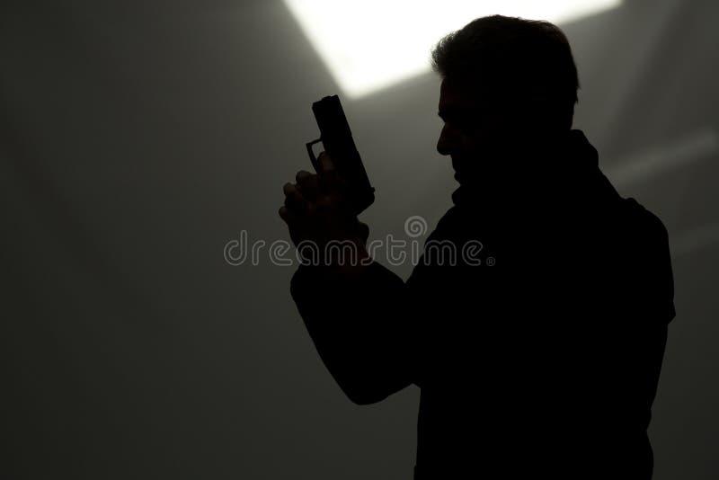 人瞄准枪的凶手警察 免版税库存照片