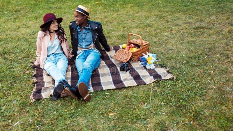 人种间微笑的夫妇坐一条毯子在公园和看 库存图片