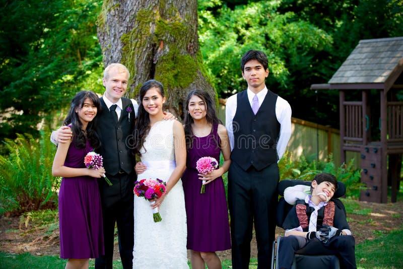 人种间婚礼 站立与他的新娘的增殖比的新郎 库存照片