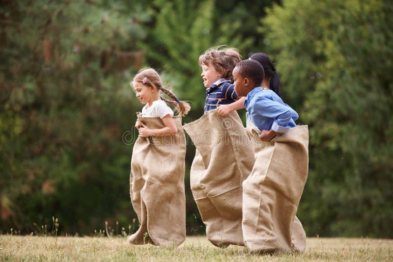 人种间小组在套袋跑的孩子 库存图片