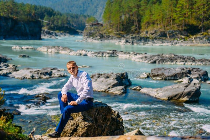 人穿戴了企业衣裳坐岩石由河和山 免版税库存照片