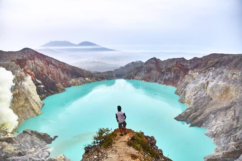人站立在火山和神色顶部在火山口的湖 免版税图库摄影