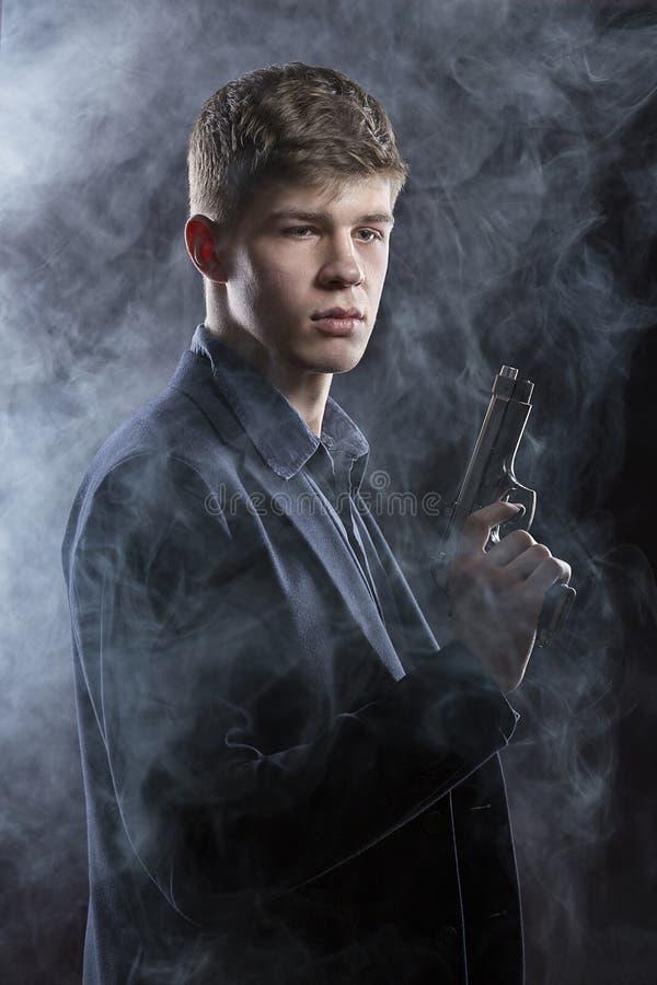 年轻人纵向有枪的 可能 免版税库存图片