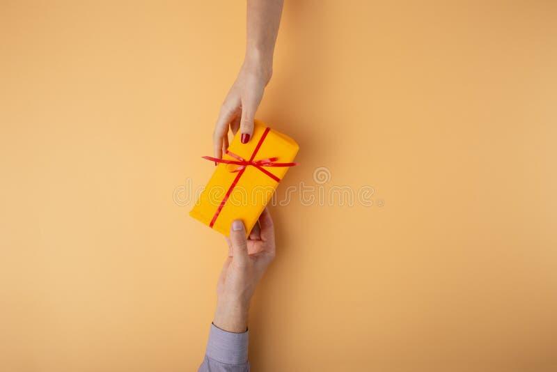 人给女孩从接近的一件礼物,在装饰纸包裹的箱子有弓橙色背景,假日的概念, 图库摄影
