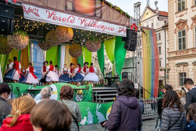 人群在阶段观看小学生执行在Pragues复活节市场庆祝期间在老城广场 库存图片