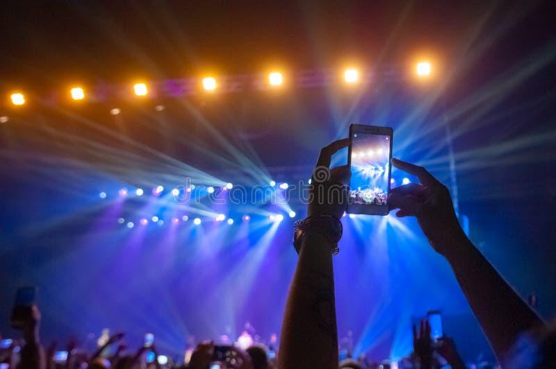 人群的人们在音乐会做录影记录和pics 免版税库存图片