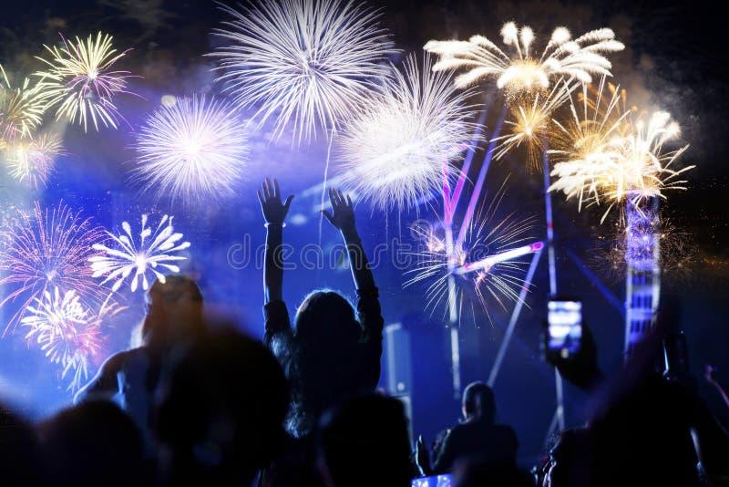 人群观看的烟花-新年庆祝抽象假日背景 免版税库存图片