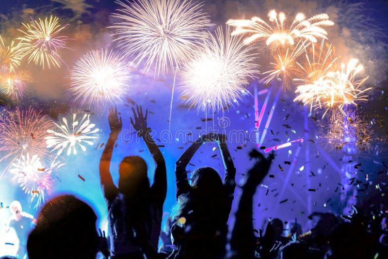 人群观看的烟花-新年庆祝抽象假日背景 免版税库存照片