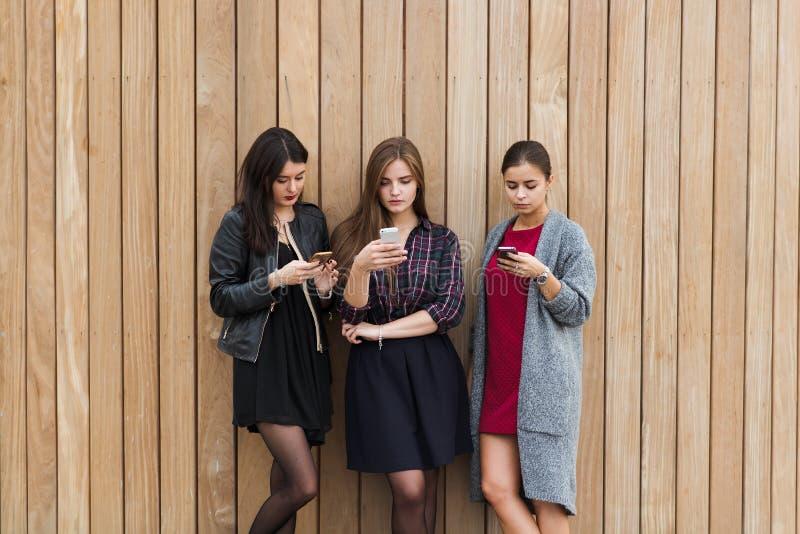 年轻人聊天在手机的三名妇女,当一起站立户外反对与拷贝空白区时的木墙壁背景, 免版税图库摄影