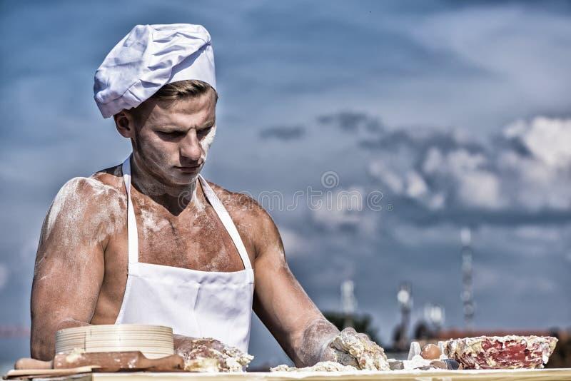 人肌肉面包师或烹调在碗的揉的面团 E 贝克在用面粉报道的加工面,揉 免版税库存照片