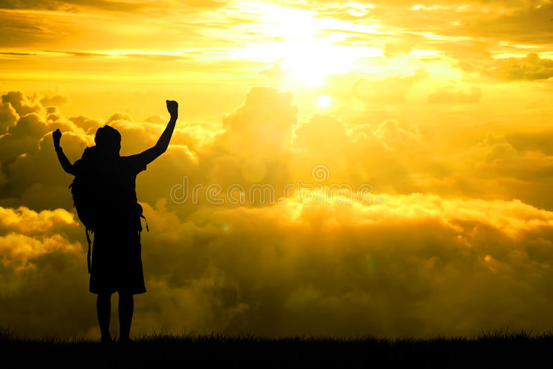 人背包徒步旅行者开放胳膊剪影上升了往在希望天空在日落光线影响、概念生活成就的和succes 免版税库存图片