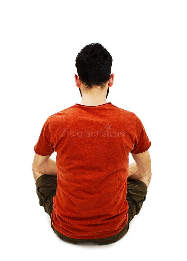 年轻人背面图坐地板 免版税库存照片