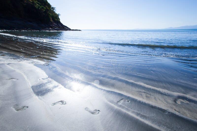 人脚脚印在黑沙滩的在晴朗的夏天 免版税库存图片