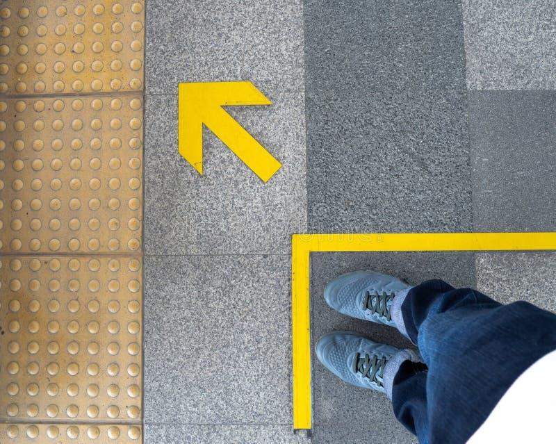 人脚顶视图站立在地铁平台的箭头标志的 在地板上的黄色箭头标志在火车站 库存照片