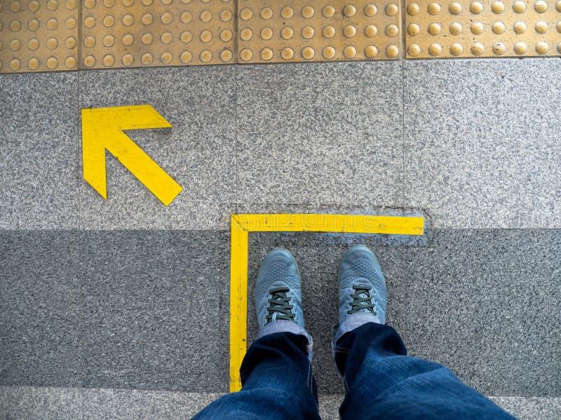 人脚顶视图站立在地铁平台的箭头标志的 在地板上的黄色箭头标志在火车站 免版税库存照片