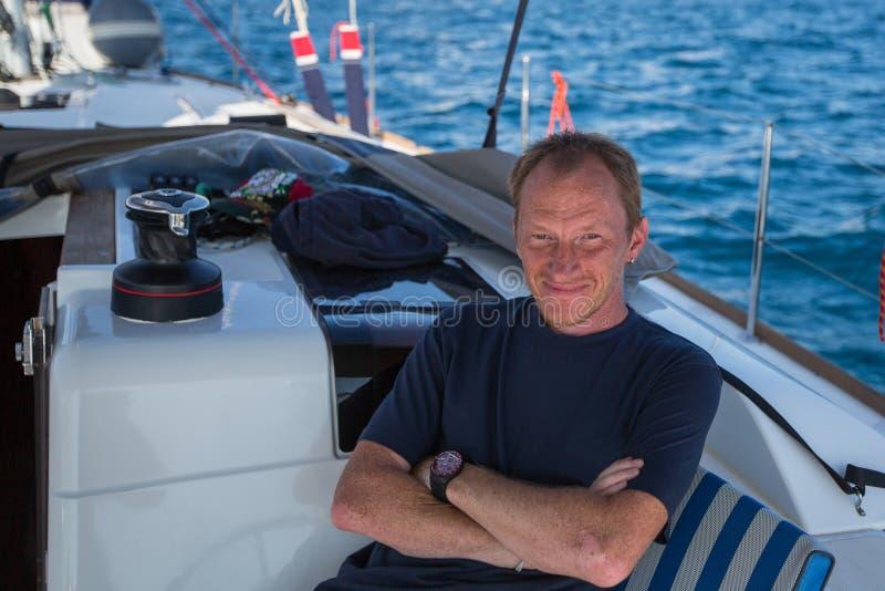 人船长坐他的风帆游艇 库存图片