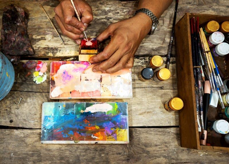 人艺术家通过画抽象创造一张绘画 工作环境在办公室,顶视图 库存图片