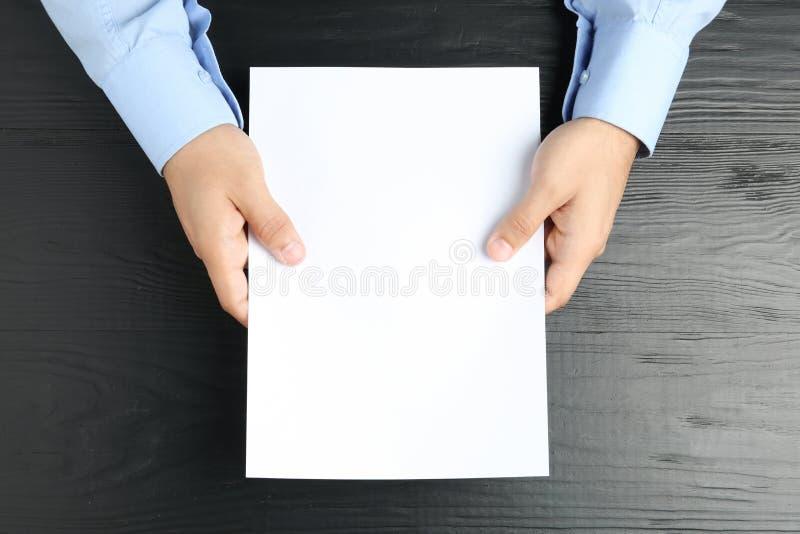人藏品小册子的白纸板料在黑木桌,顶视图上 免版税库存照片
