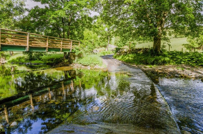 人行桥和浅滩在一条小河在一个树木繁茂区 库存照片