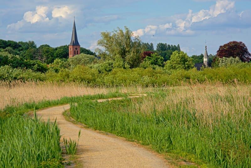 人行道穿过河斯海尔德河,富兰德,比利时开拓地有一点教会的 图库摄影