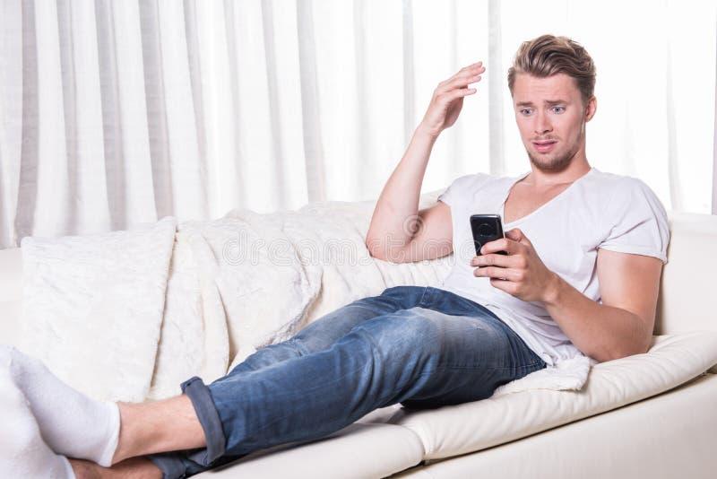 年轻人被惊吓关于在智能手机的消息 库存照片