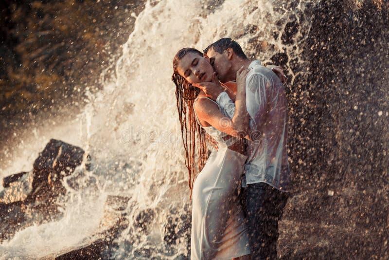 年轻人被迷恋的夫妇拥抱和亲吻在瀑布下浪花  图库摄影