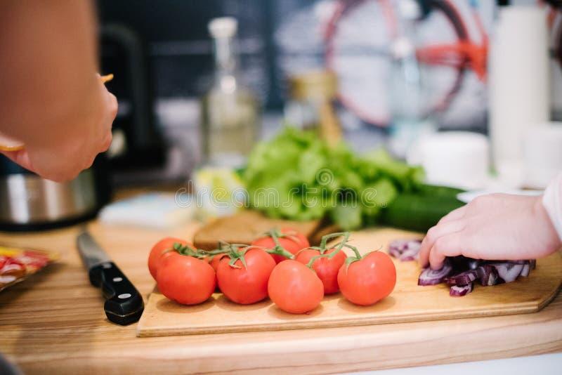 人裁减蕃茄和其他菜与一把刀子在一个木切板 库存照片