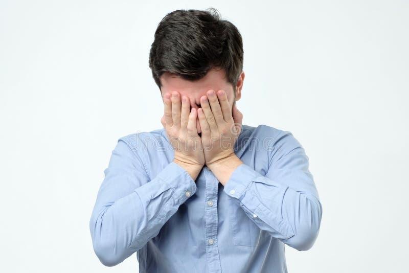 人覆盖物面孔用手,当站立反对灰色背景时 免版税库存照片