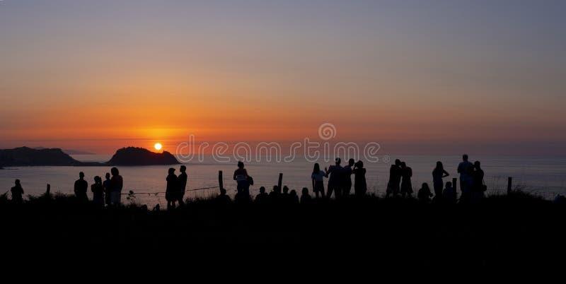 人观看的太阳剪影设置了在海,巴斯克地区 免版税图库摄影
