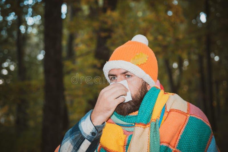 人解决,在他病的吹的鼻子和打喷嚏,咳嗽后 吹他的在薄纸的被传染的人鼻子由于 免版税库存图片
