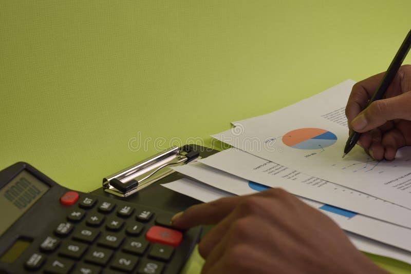 人计算财政预算的费用和的分析 在笔的选择聚焦 免版税库存照片