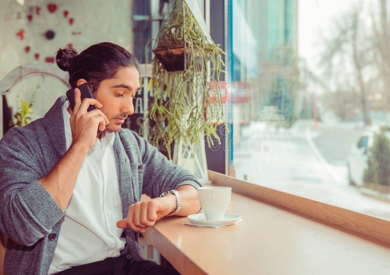 人讲话由看手表的智能手机检查时间 免版税库存图片