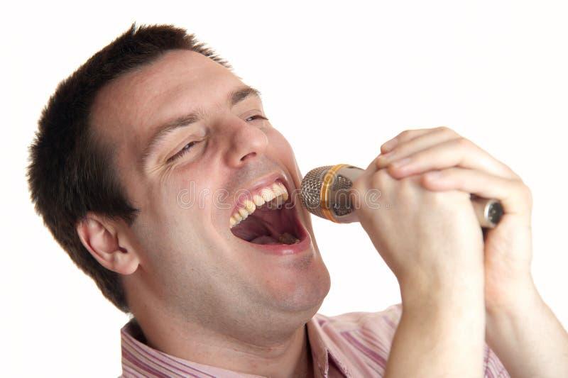 人话筒唱歌年轻人 免版税库存照片