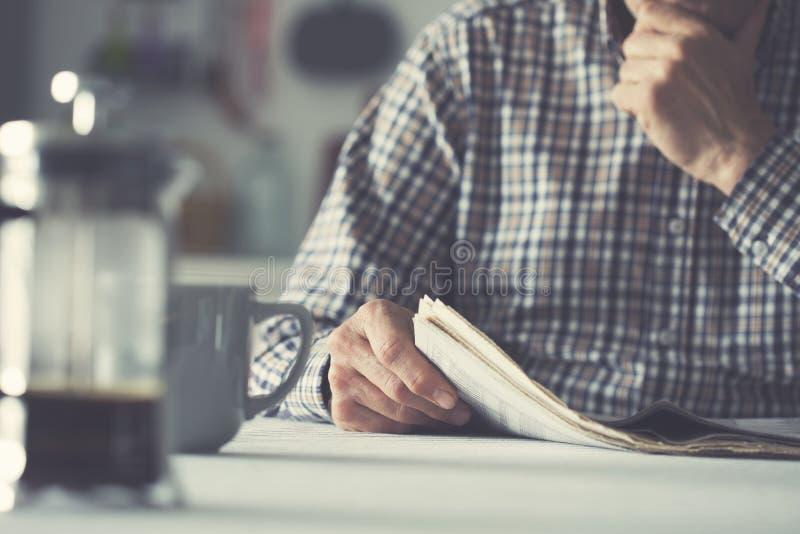 人读书报纸和饮用的咖啡 库存照片