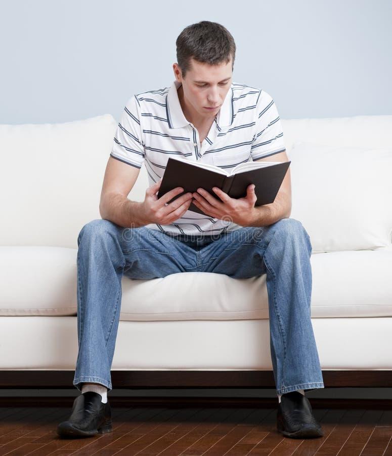 人读取坐的沙发年轻人 图库摄影