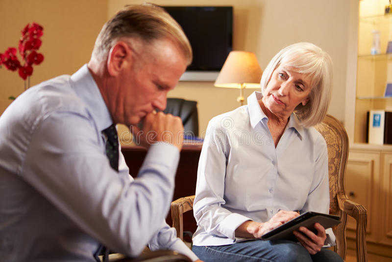人谈话与使用数字式选项的女性顾问 免版税库存图片