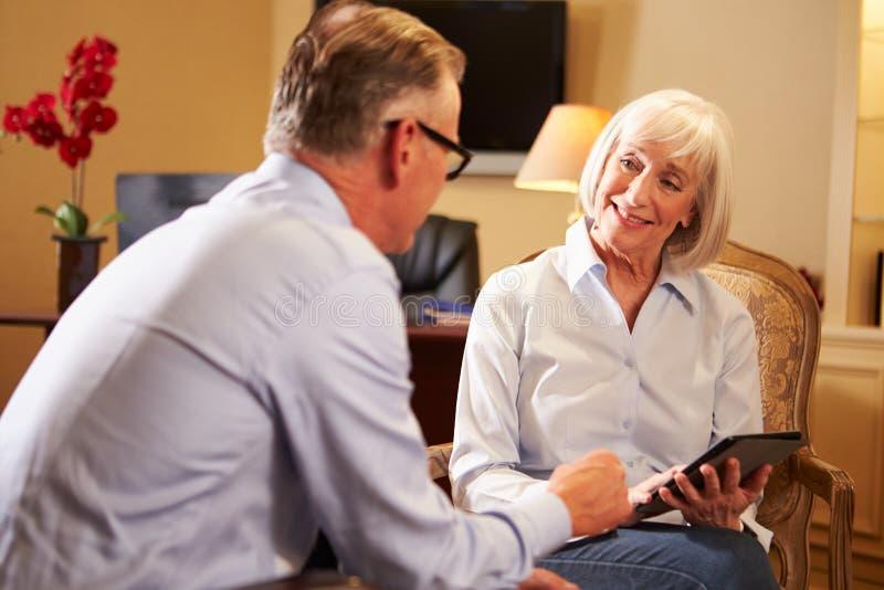 人谈话与使用数字式选项的女性顾问 库存图片