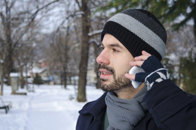 人谈话在一个智能手机在冬天 库存图片