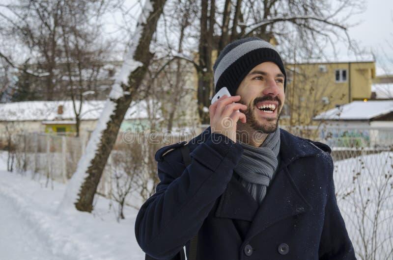 年轻人谈话在一个智能手机在冬天 免版税库存图片