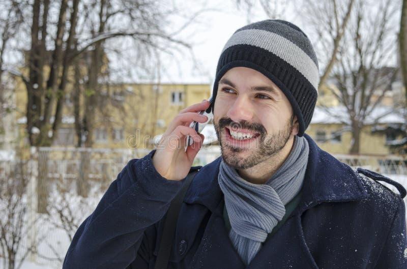 年轻人谈话在一个智能手机在冬天 图库摄影