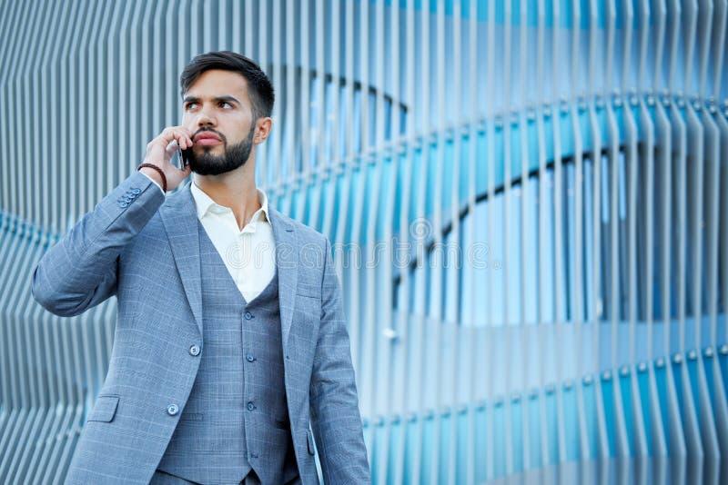 人谈话在智能手机 使用手机的商人都市专业商人 愉快的专业佩带的衣服夹克 免版税库存图片
