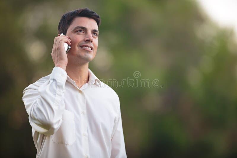 年轻人谈话在电话户外 库存照片