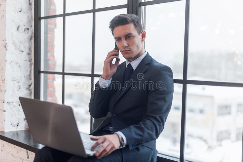 年轻人谈话在他的手机在办公室 免版税库存图片