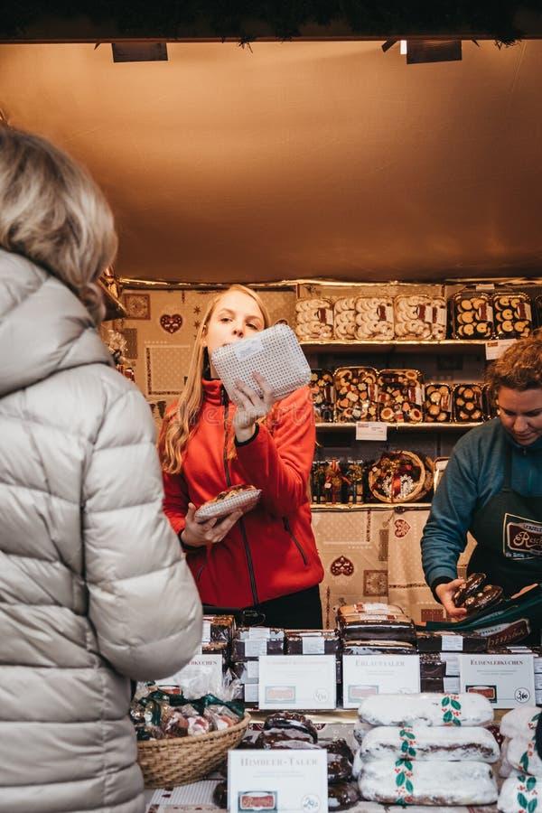 人购买甜点在美泉宫,维也纳,奥地利的圣诞节和新年的市场上 图库摄影