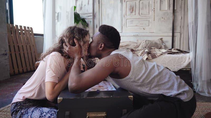人赢取棋和舞蹈 多种族夫妇亲吻和互相震动手 妇女对胜利祝贺 免版税库存图片