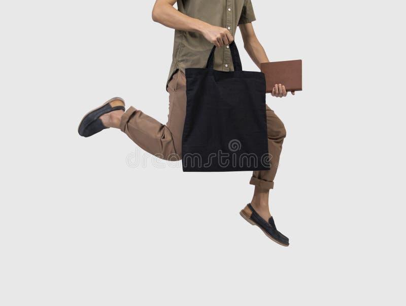 人跃迁拿着袋子大模型空白模板的帆布织品 免版税图库摄影