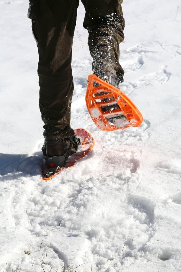 人跑与在山的雪靴在白色雪 免版税库存照片