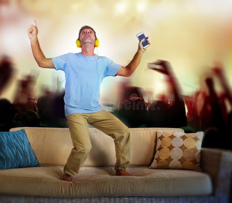 人跳在沙发长沙发的听到与手机的音乐和耳机想象作为著名摇滚乐队音乐会并且扇动audienc 免版税库存图片