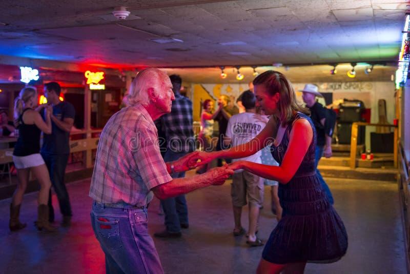 人跳舞的乡村音乐在残破的轮幅舞厅里在奥斯汀,得克萨斯 图库摄影