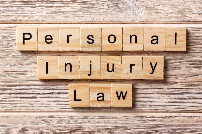 人身受伤在木刻写的法律词 人身受伤在桌上的法律文本,概念 免版税图库摄影